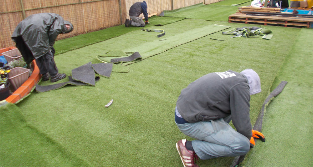 The team installing the dog run artificial turf