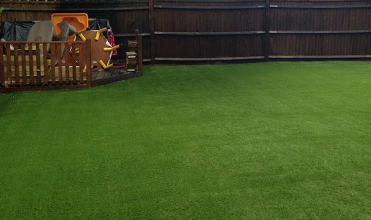 Laying artificial grass on a rubber play surface